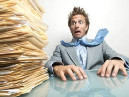 man stressed with huge pile of paperwork