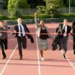 business people crossing finish line on race track