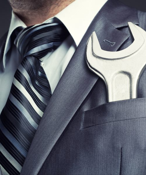 Business man with wrench in pocket